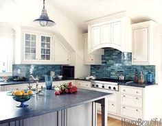 A backsplash of variegated handmade glass tiles that are reminiscent of the ocean. Design: Frank Roop.