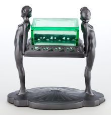 AN ART DECO PATINATED METAL FIGURAL CIGARETTE STAND AND GLASS  BOX IN THE STYLE OF FRANKART  Maker unknown, American, circa 1930  9-1/2 inches high (24.1 cm)      The removable clear green glass box supported by two female nudes  in a gunmetal patina.