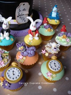"""Alice in Wonderland cupcakes created to celebrate an 18th Birthday. Cupcakes with buttercream and cupcakes domed with buttercream and fondant and topped with White Rabbit, Caterpillar, pocket watches, Cheshire cats, mushrooms and flowers, tea cups and tea pots, the magic key…... A top hat layer cake 5"""" high was also created as the top cake of the cupcake tower"""