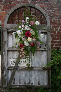 Old door used as a garden gate ~ cute rose wreath ~ love this idea