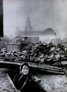 A girl emerges from a bomb shelter surounded by the ruins of Nagasaki. August 10, 1945.