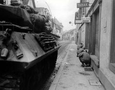 157th Regiment of the 45th Division with aid of an M10 from the 645th Tank Destroyer Battalion enters Neiderbronn, France. December 1944