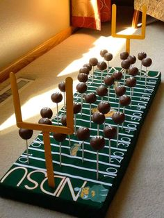 Cake pops on a football field base. Super cute alternative to a traditional football-themed groom's cake! By Courtney's Cake Pops - https://www.facebook.com/fmcakepops