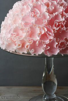 Dome-shaped cake covered with a layer of fondant, on which about 100 ruffle-blossoms are attached.