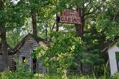 Obscured by a canopy of trees, six tiny, crumbling cabins sit next to a quiet, dead-end stretch of Route 66 that runs parallel to Interstate 44 about 10 miles outside of Rolla, Mo.