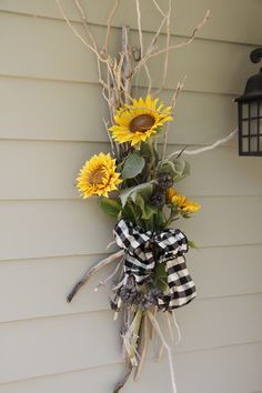 Especially the big blk/wht checkered bow with Sunflower - Arrangement outside with driftwood by Anne Jones