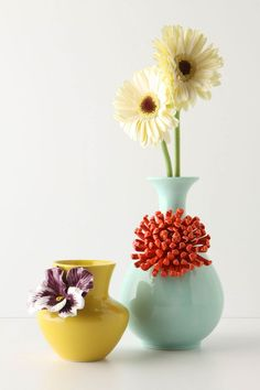 1. Buy cheap vase at dollar store or thrift shop. 2. Spray paint 3. Attach decorative flower/decal to front. Maybe $10?   OR go to Anthropologie blue chrysanthemum vase $28