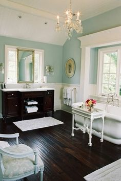 Beautiful colour for a bathroom - tiffany blue. Love the chandelier and the way the blue and white play together to make a crisp and clean feeling.  The darker wood accents keep it from floating away.