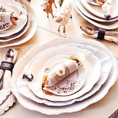 Elegant Table Setting:   Ready to showcase the Christmas feast, these stacks of mismatched white plates will make food colorful and appetizing. Elegantly embellished English crackers continue the tone-on-tone color scheme. Christmas tree candle clips attached to each plate add a warming holiday touch.