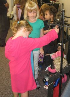 Pulling strings to make the puppets go, kids get absorbed in Mountain Marionette's marionettes at last week's Library event.