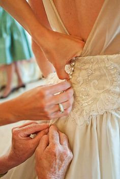 Buttoning the Dress - Image © donmirraweddings.com