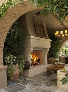 Love this outdoor fireplace also the candle chandelier