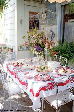 Llovely outdoor dining spot - love the vintage tablecloth and decor