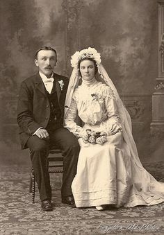 Circa 1900 couple both sitting down, a pose rarely seen.  The bride's white dress is pigeon breasted, she has flowers and trailing vines on her beautiful bridal bonnet, wearing a corsage and she carries a bouquet. The groom wears a white bow tie and a boutonniere.