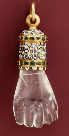 Hand shaped Pendant. Circa 1600-1650. Made of rock crystal, with enameled gold mount set with emeralds.