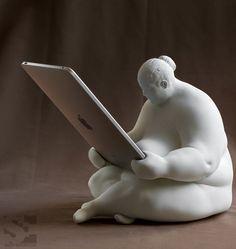 """A criação é de Scott Eaton e sem dúvida um dos docks de iPad mais divertidos que eu já vi! Batizada de """"Venus of Cupertino"""" a rechonchuda moça segura qualquer uma das gerações de iPad, enquanto os carrega e sincroniza, graças a um discreto carregador em sua barriguinha. Recém finalizada, ela estará à venda em breve"""