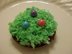 GP Easter egg hunt brownie made w/Wilton 12 cavity whoopee pie/muffin top pan, spread w/small amt of chocolate frosting, topped w/coconut dyed green, patted down on chocolate frosting to adhere, & pastel Sixlet candies (found at ACMoore) w/small smear of frosting to adhere to the coconut - reminds people of a Mounds bar