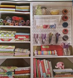 Metal pegboard w/ shelving and bins and rolling fabric squares for organizing studio sewing