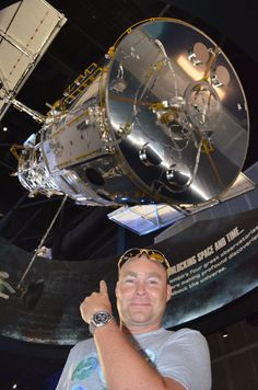 Pete Murden wears his #Omega Speedmaster Moonwatch Apollo Soyuz Limited Edition with meteorite dial, while posing in front of a replica of the Hubble Space Telescope at the Kennedy Space Center.
