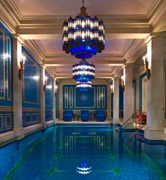 This amazing indoor swimming pool is located in Gerald Ford's mansion in Dallas. It contains elaborate wall sconces, blue tiled pattern walls, tiled swimming pool, 3 crystal chandeliers, coffered ceilings, and lounge chairs.