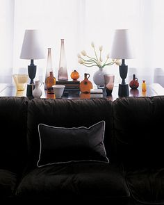 Bold Brown  In a luminous white setting, dark brown has the impact of black, without the harshness. This sofa is upholstered with velvet the color of bittersweet chocolate; white piping makes the fabric look even darker. A varied collection of smoky-glass bottles and vases lightens the mood.