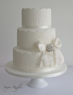 Lace Wedding Cake with vintage style brooch- some peach/coral would be nice