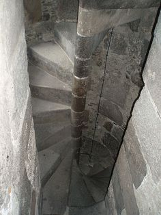 Spiral stairs in medieval times were generally made of stone and typically wound in a clockwise direction (from the ascenders point of view), to place attacking swordsmen (who were most often right-handed) at a disadvantage. This asymmetry forces the right-handed swordsman to engage the central pike and degrade his mobility compared with the defender who is facing down the stairs.