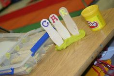 These are popsicle sticks poked into Play Doh so they will stand. On the sticks there are foam craft letters.