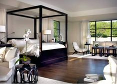 Zen modern island bedroom design with black wood canopy bed, crisp white hotel bedding with blue trim, glossy black lacquer barrel accent table, ivory drapes, wood floors and small sitting area. soft gray paint wall colors. white black gray bedroom colors.