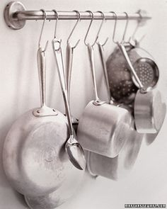 A handrail and several S-hooks will turn a few square feet of wall into a convenient rack for kitchenware.