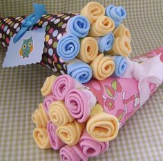 bouquet of onesies, burpcloths, swaddling blankets- great gift idea for baby shower.