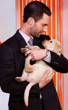 Adam Levine cuddles with a puppy. Too much cuteness!