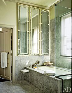 A mirrored screen conceived by MGM costume designer Adrian shines in the master bath of a home in New Orleans; the tub fittings are by Kohler, and the walls, tub surround, and floor are surfaced with Carrara marble.