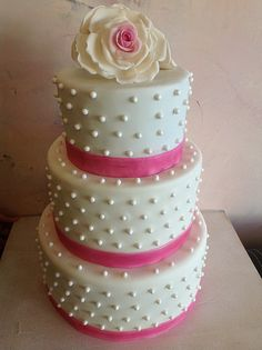Pearly Fun Wedding  Top tier is Marble Cake with Mocha Buttercream Filling, Bottom Two Tiers Are VanillaBean Cake with Pineapple Buttercream Filling. Covered in Dark and White Chocolate Ganache and Finished in Homemade MMF. pearls are Sugar, roses and ribbon are fondant.