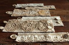 a great and easy thing to make with my ever-growing stash of lace, ribbons and doilies. these bracelets in various widths are all sewn on heavy linen ground, with a button and ribbon-loop closure.