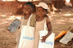 Girls walk arm-in-arm outside Likoli, a UNICEF-supported primary school in the village of Zakpota, in central Benin. UNICEF provides Likoli and surrounding schools with supplies, classroom furniture, and training for teachers. One girl carries a UNICEF-supplied slate. Their book bags bear the UNICEF logo.    © UNICEF/NYHQ2006-2866/Julie Pudlowski  http://www.unicef.org