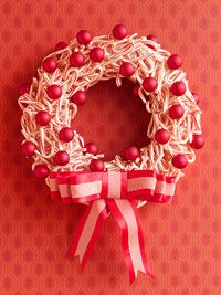 mini candy canes, foam wreath wrapped w/white satin ribbon.  Hot glue candy canes every which way in layers. Hot glue red ornaments  and ribbon and bow  CUTENESS