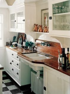 White kitchen, wood counters, cup pulls, copper