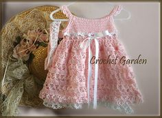 Love knots are the special accent in this lovely crochet baby dress designed by Lisa Naskrent of Crochet Garden.