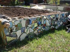 LOVE!  Cement block raised beds covered with mosaic pique assiette.