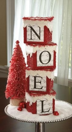 Christmas Crafts - maybe wood blocks or clear photo blocks covered in red lace or fabric. Looks like white snow paint and then sheet music printed with the letters overlayed on them (Word would do that). ModgePodge on? Tops with a ribbon around the edging