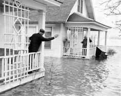 In April 1960, the Elkhorn River flooded, leaving homes surrounded by high water. H.H. Lallman, left, chats with Chris Martinsen and Johanna Keilstrup in Winslow, Nebraska, during the flood. THE WORLD-HERALD