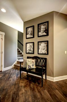 The angled dark flooring allows your eye to travel towards the main focus of this entryway where theres a showcase of family portraits, and the bench. Just as well the colour pallet of the walls are perfectly chosen to be matched with the hardwood.