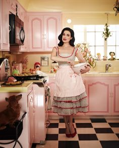 Dita Von Teese in her Los Angeles, CA kitchen. I don't know where to pin this - love her, her outfit, and her kitchen. Dommage! #DitaVonTeese #Kitchens #Vintage #Retro #Pink #Yellow