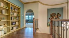 The staircase in this Bridges of Las Colinas #model #home lead up to a beautiful #hallway with #wood #floors and spacious #game #room. #staircase #landing #bookshelf