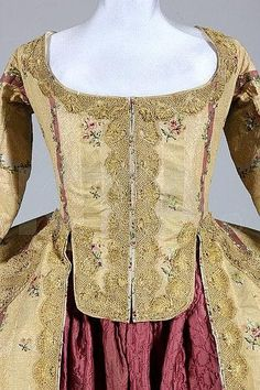 Detail front view, robe à la francaise, Italy or Spain, c. 1770. Gold brocaded striped silk, woven with puce and silver bands within the textured cloth of gold stripes, pretty floral sprigs and trails, edged and trimmed with scalloped gold bobbin lace. Lined in ivory taffeta.