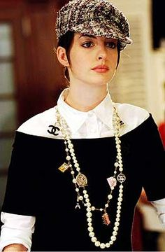The clothing in this outfit featured a black boat neck top by David Rodriguez worn over a white shirt from Miu Miu. The costume was completed with Anne Hathaway wearing a Chanel newsboy cap and that famous Chanel Parisian Charm necklace and two strands of white pearls. Now this piece is tough to find. The Chanel Boutiques tell us it is discontinued. Occasionally you can find one on ebay.