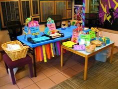Summer Reading Supply Table.  Overwhelm the children with colorful party decorations and graphics of cute animals reading books and they won't be able to help but pick up a reading log. That's the theory, anyway. (Rachel Moani)