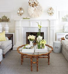 living rooms - Cameroon Juju hat white ginger jars gray jute rug white garden stool gray sofa chairs marble fireplace Kelly Wearstler citrine imperial trellis pillows