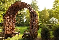 What an inviting bench arbor. The twists and crags of the wood are just gorgeous. By Laura Spector Design.